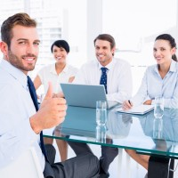 Executive gesturing thumbs up with recruiters during interview